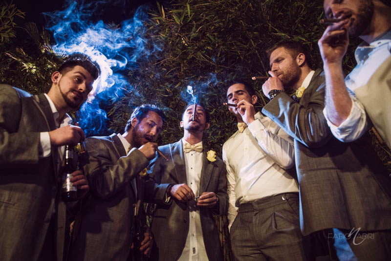 Groom groomsmen smoking cigar