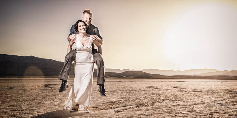 Bride groom piggy back desert photo