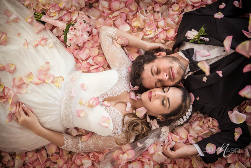 Bride groom lying ground covered by pink roses