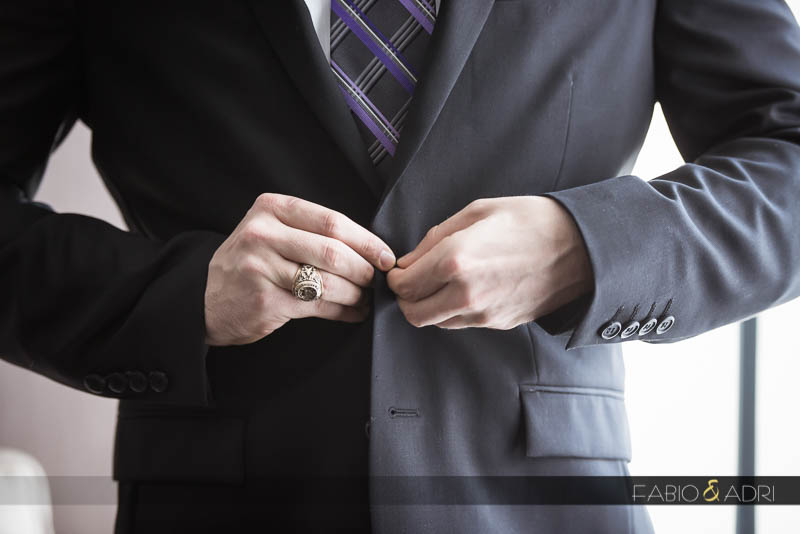 Groom buttoning up suit
