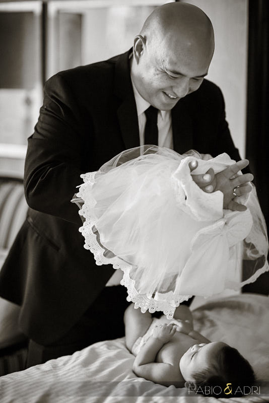 Groom dressing up baby daughter