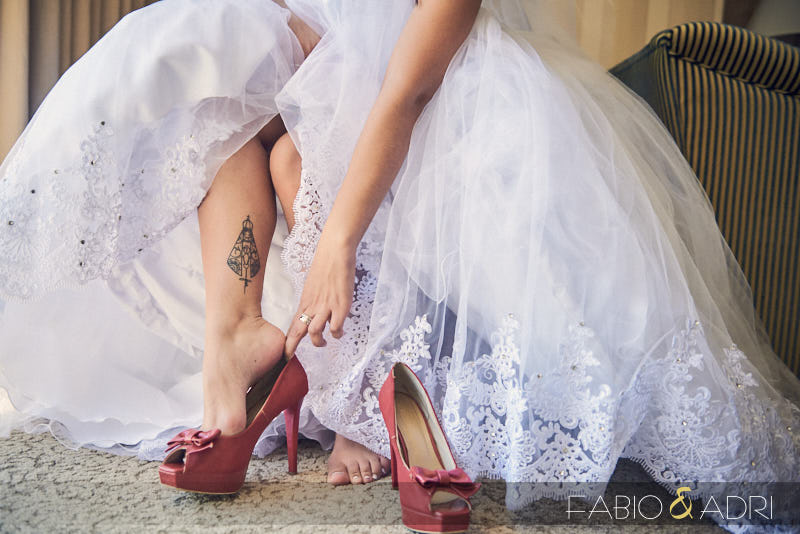 Bride Putting On Red Shoes