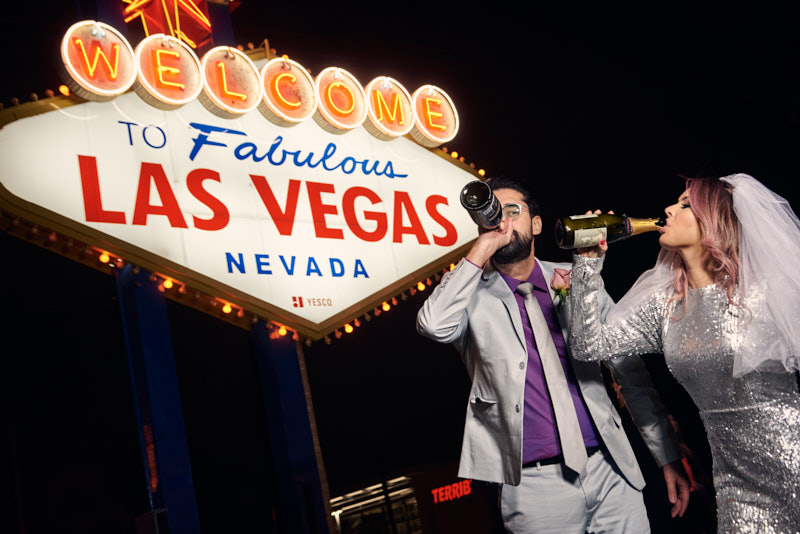 Bride and Groom Drinking Champagne from Bottle Las Vegas Sign
